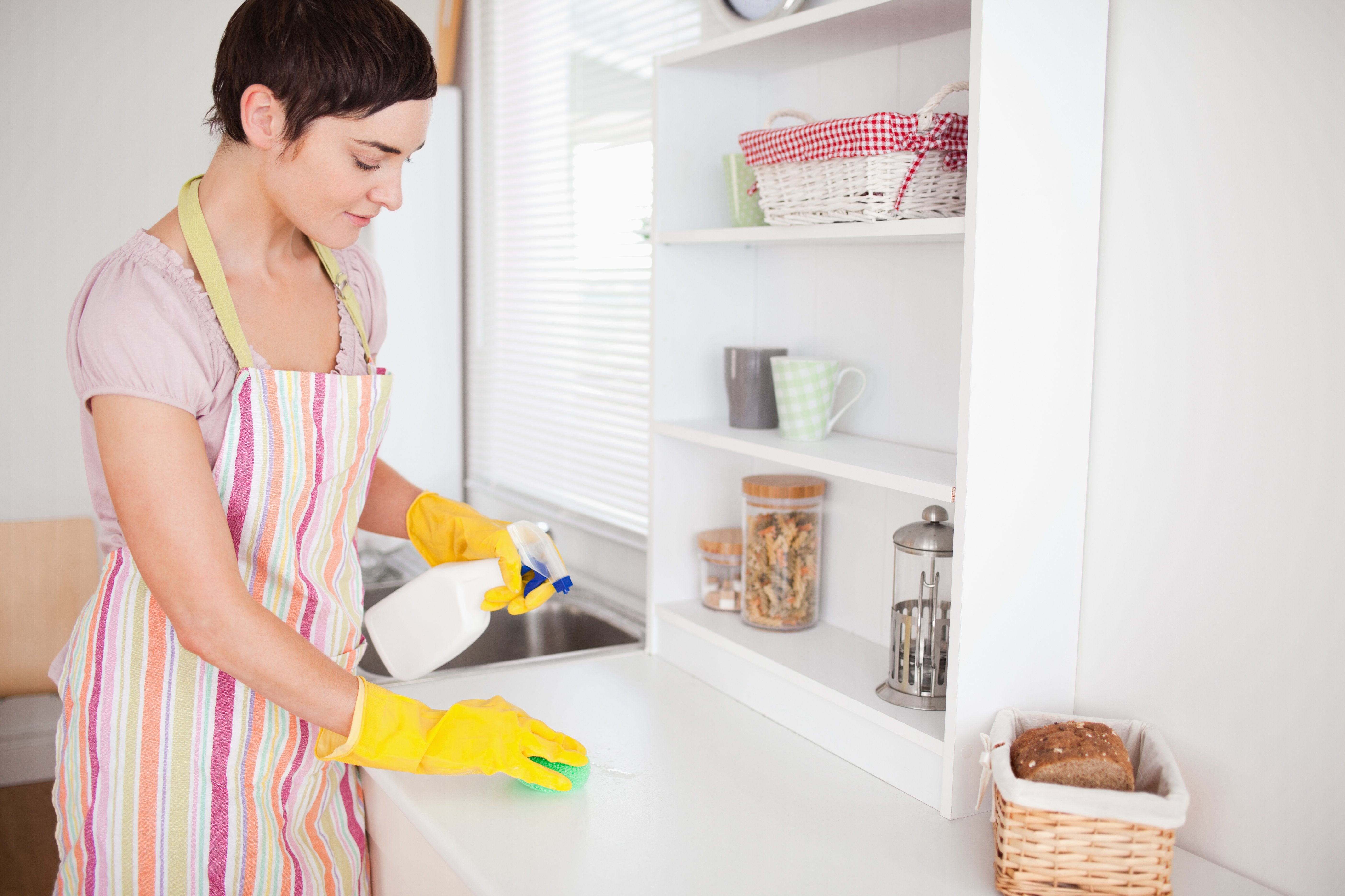 Beautiful brunette woman cleaning a cupboard in the kitchen-1