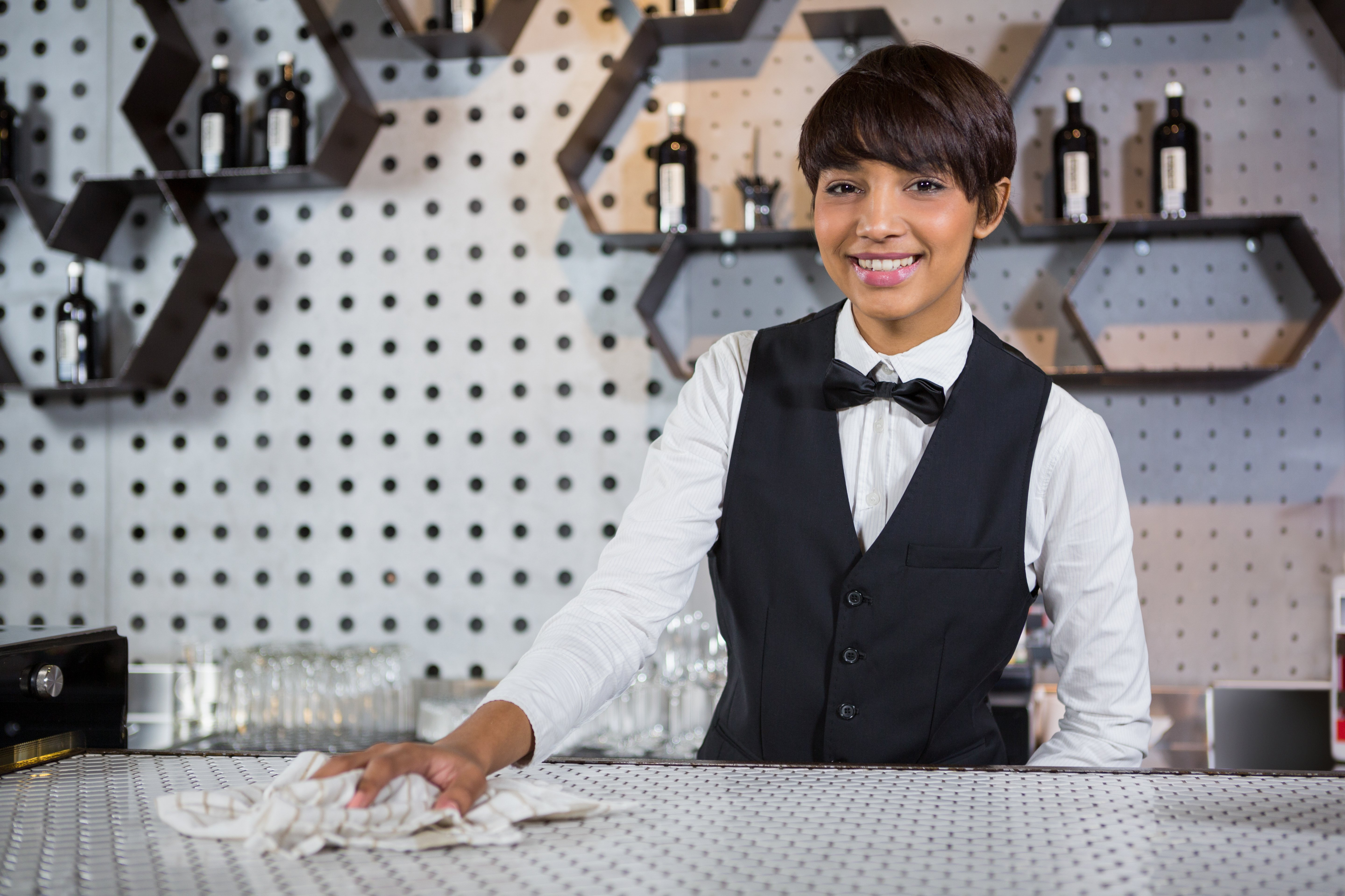 Portrait of smiling waitress cleaning bar counter in bar